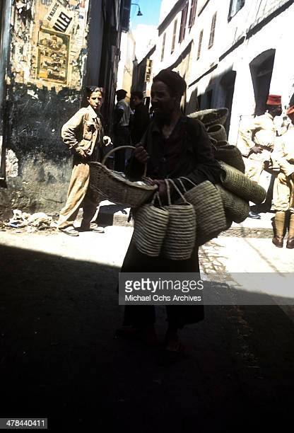 A local women carries baskets in the Casbah of Algiers Algeria Off limits to US servicemen and patrolled by Military Police French and Algerian Police