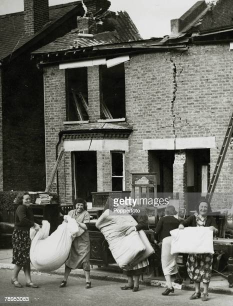 circa 1940 Britain Women cheerfully salvage some belongings from bombed out houses in Bromley Kent hit by German bombs