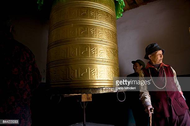 Local women spinning a prayer wheel on the side of the road from Shangri La to Yading a reserve in southwest Sichuan Province China This area of...