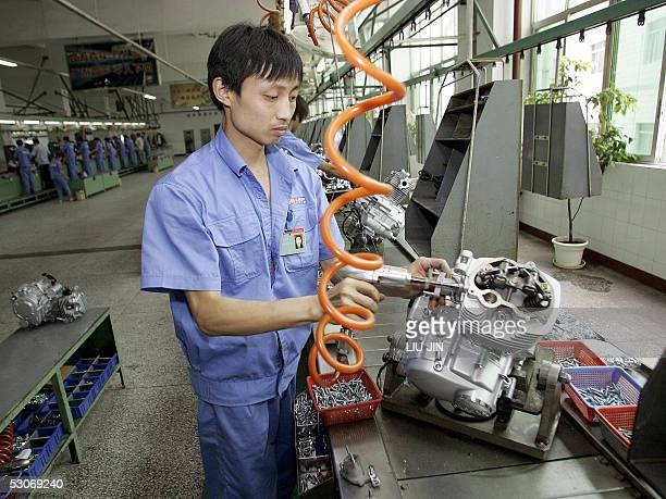 A local worker assembles an engine of a motorbike at the Lifan Group's factory in southwest China's Chongqing city 31 May 2005 Capitalism is on the...