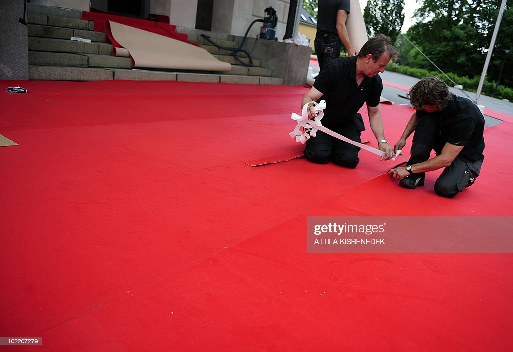 Local workers fix a red carpet in front of the Eric Ericson Hall of Skeppsholen in Stockholm on June 18, 2010 prior to a gala dinner organized by the local government. Swedish capital is filling up with royalties from all over Europe for the upcoming wedding of Sweden's Crown Princess Victoria and Daniel Westling on June 19, 2010.