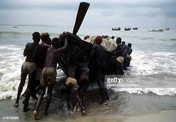 Local workers push a row boat into the surf in Accra Ghana