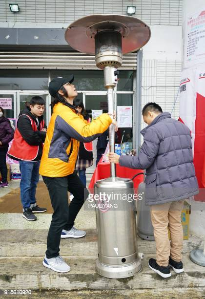 Local workers set up a heater outside a local detention centre being used for families displaced in Hualien on February 8 after the city was hit by a...