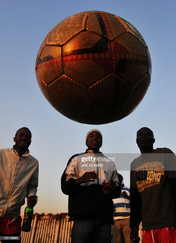 Local young men watch their friends to play football at Mamelodi township in Pretoria on June 16, 2010,during the 2010 World Cup football tournament in South Africa.