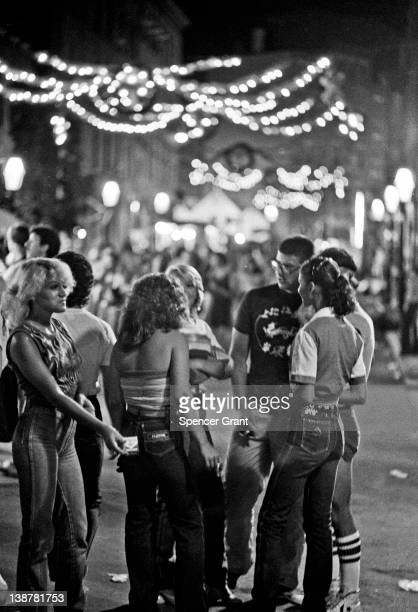 Local young people congregate under the light of the Festival of Saint Rocco on Hanover Street in the predominantly ethnic Italian North End...