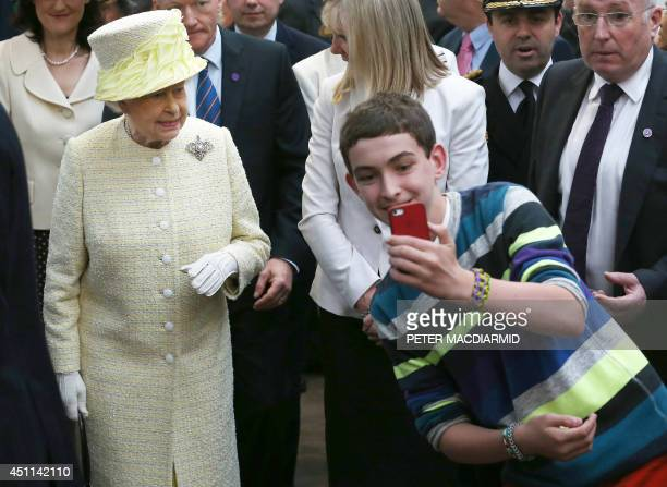 A local youth takes a selfie photograph in front of Queen Elizabeth II during a visit to St George's indoor market on June 24 2014 in Belfast...