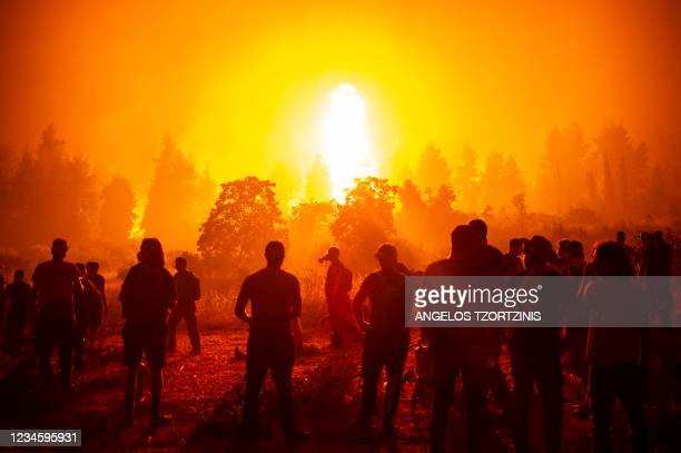 Local youths and volunteers gather in an open field and wait to support firefighters during a wildfire next to the village of Kamatriades, near...