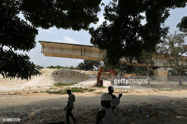 Local youths stand in the shade of a tree near an unfinished bridge under construction in Bodo Nigeria Wednesday Jan 13 2016 Twenty years after the...