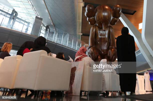 Locals and foreigners gather near an artwork by US artist Brian Donnelly entitled 'small lie' at Hamad International Airport in the capital Doha on...