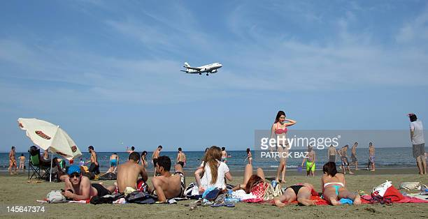 Locals and holiday makers sunbathe at McKenzie beach as a passenger plane approaches Larnaca airport on the southern coast of the east Mediterranean...