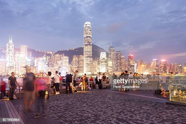 Locals And Tourist Enjoying Hong Kong Skyline From The Avenue Of Stars At Dusk