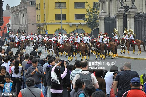 Locals and tourists are observing the Húsares de Junín horse mounted cavalry presidential guard at the Presidential Palace in old historic downtown...