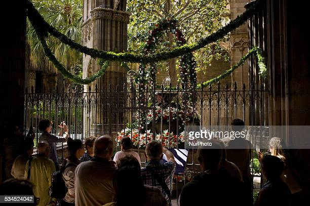 Locals and tourists contemplate the dancing egg at the cloister of the Barcelona Cathedral Spain on 26 May 2016 The dancing egg is an old tradition...
