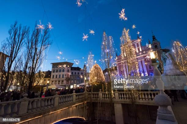 Locals and tourists cross the Triple Bridge on December 2 2017 in Ljubljana Slovenia The traditional Christmas market and lights will stay until 1st...
