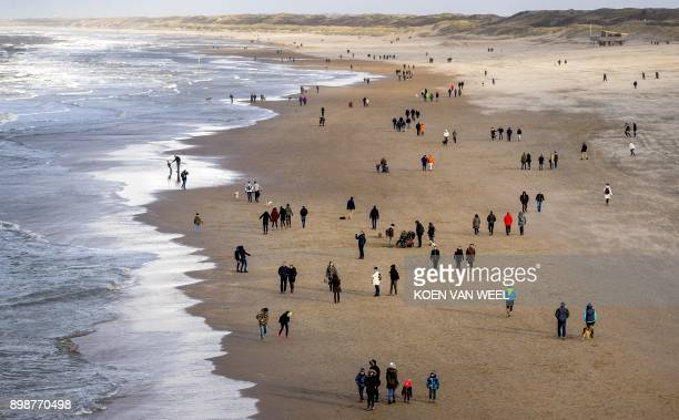 Locals and tourists enjoy a walk at Scheveningen beach in the Netherlands on December 26 on the second day of the Christmas holidays / AFP PHOTO /...