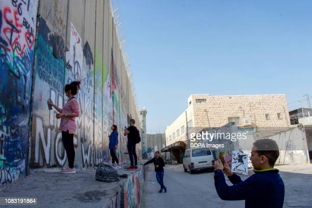 Locals and tourists seen spraying and painting graffiti on the West Bank Separation Wall The Israeli Separation Wall is a dividing barrier that...