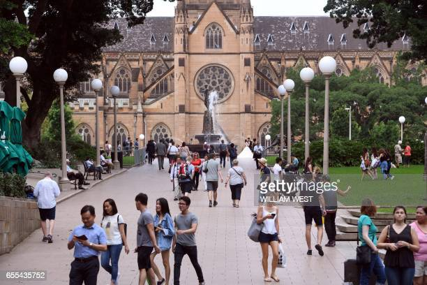 Locals and tourists walk through Sydney's Hyde Park towards St Mary's Cathedral on March 20 2017 / AFP PHOTO / William WEST