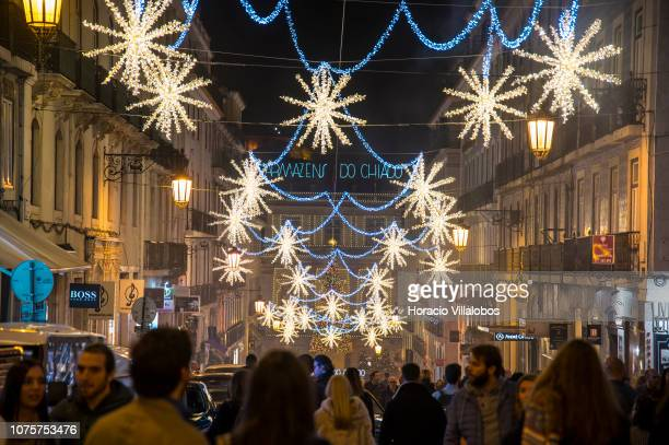Locals and tourists walk under Christmas and New Year light displays in Rua Garrett on December 01, 2018 in Lisbon, Portugal. The city shows a...