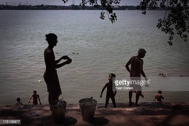 Locals bathing at a ghat along the banks of the Hooghly river in Kolkata Kolkata is India's oldest port city It is a place of sharp contrasts Though...