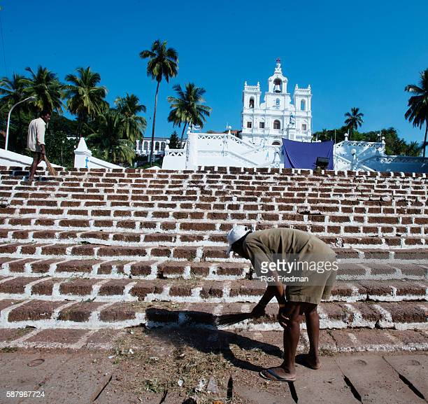Locals brushing steps off at the India Church of our Lady of the Immaculate Conception in Panaji the capital city of Goa India on December 1 2014