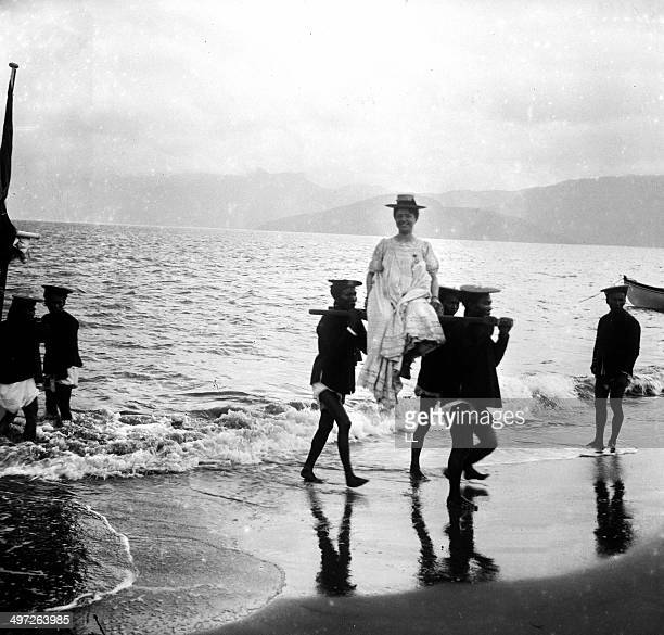 Locals carry a French woman to shore on an improvised litter as she arrives at Tonkin Vietnam by boat 1902