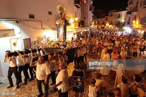 Locals carry a statue of the Virgin Mary during the annual Santa Maria de las Nieves procession in the city's old town on the island of Ibiza on...