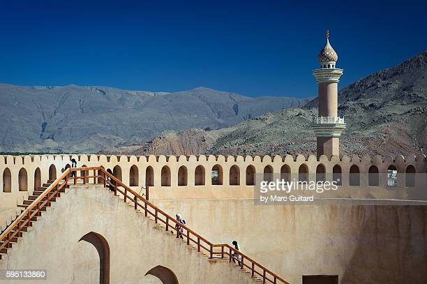 Locals climbing the stairs of Nizwa Fort, for a view of Nizwa, with Jebel Shams in the background.
