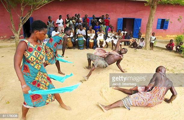 Locals dance during a performance at the Kopeyia drumming village in Ghana, May 8, 2004. The cloth depicts former Ghanaian dictator J. J. Rawlings....