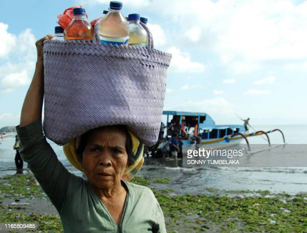"""Locals disembark at a beach in Denpasar in Indonesia's resort island of Bali from a """"perahu"""", a wooden outrigger commuter boat, a popular mode of sea..."""