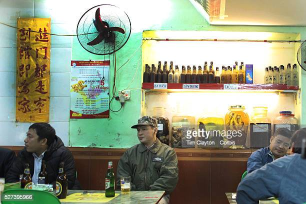 Locals drink beer in a bar on a street corner in the old quarter of Hanoi Vietnam Sitting behind the patrons are various vodka drinks including 'bear...