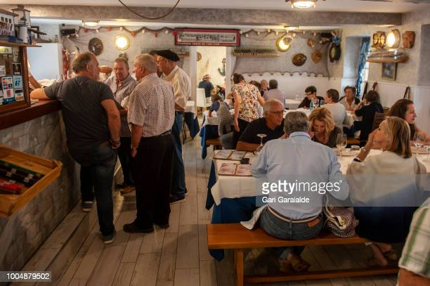 Locals drink everyday wine at the Restaurante Hermandad de Pescadores bar while people have lunch on July 20 2018 in Hondarribia Spain The restaurant...