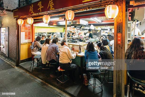 Locals eating ramen at the restaurant in Takitory alley in Shinjuku, Tokyo, Japan