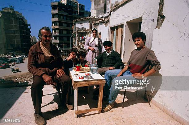 Locals enjoy a quiet moment, during a lull in the fighting outside their war-torn houses with some drinks and some cigarettes..