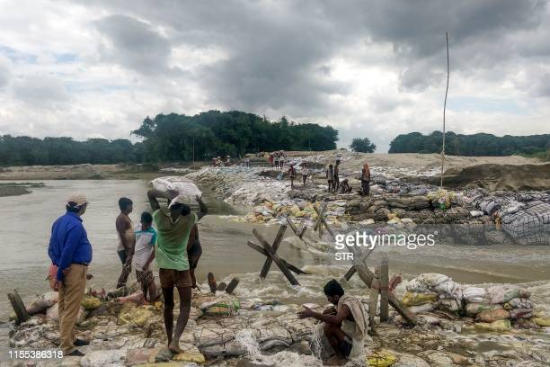 TOPSHOT Locals gather concrete fragments and heavy bags wrapped in nets to build a dam as floodwaters flow from the north into the state of Indian...