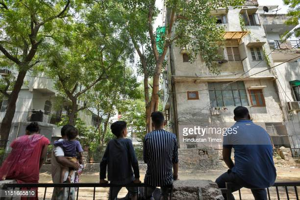 Locals gather near the house where an elderly couple along with their domestic help were found murdered, at Vasant Apartments, in Vasant Vihar on...