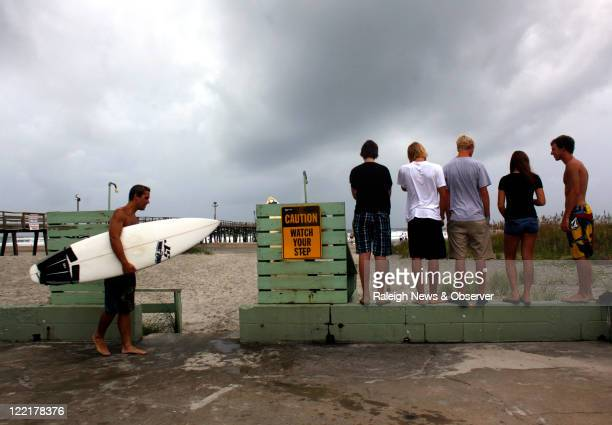 Locals gather near the Oceanana Pier Friday August 26 in Atlantic Beach North Carolina to watch waves and surfers Hurricane Irene could make landfall...
