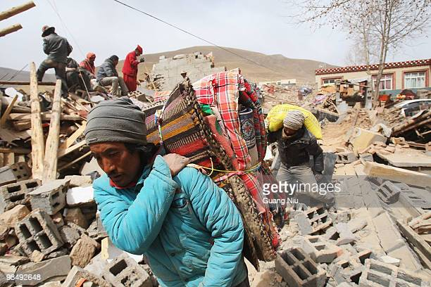 Locals gather their belongings and move them out through the rubble following a strong earthquake on April 16, 2010 in Jiegu, near Golmud, China. It...