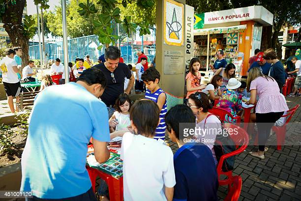 Locals gather to swap their Panini 2014 FIFA World Cup Brazil stickers at Praça Popular on June 21 2014 in Cuiaba Brazil