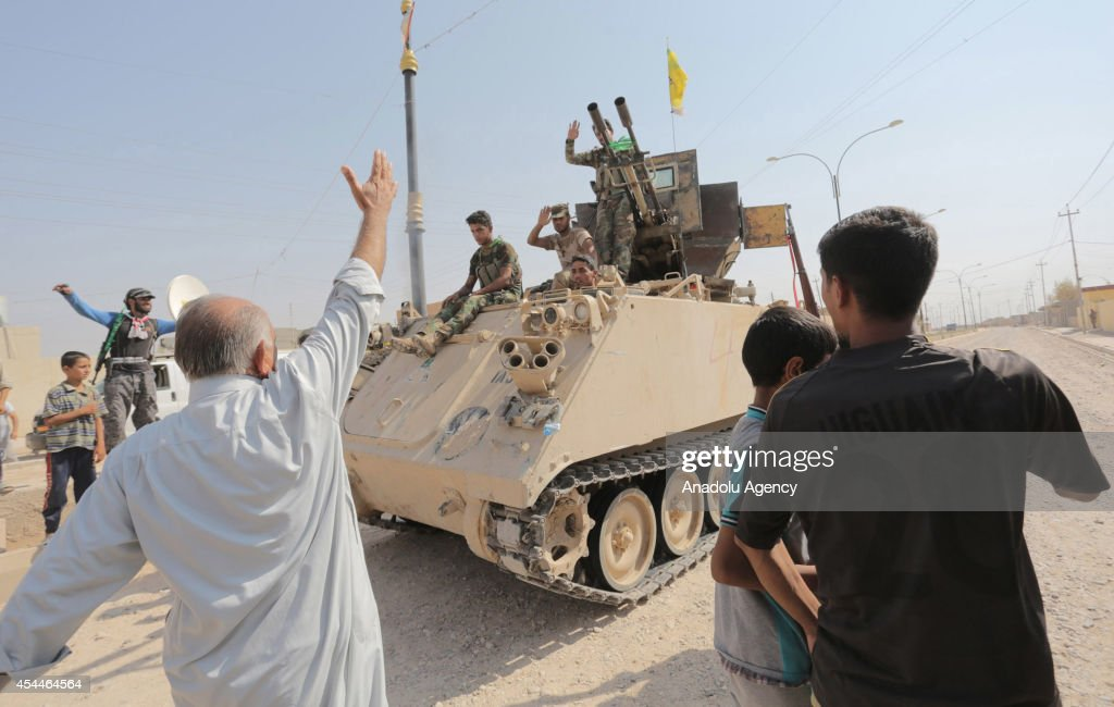 Locals greet the soldiers after Iraqi forces have entered the northern town of Amirli which had been under the siege of Islamic State militants for over two months in Saladin ,Iraq on September 1, 2014. Supported by Kurdish forces and Shiite militias, the Iraqi army launched an offensive shortly after the U.S. carried out airstrikes against Islamic State (IS) positions near the town, and dropped aid for the nearly 20,000 Shiite Turkmen trapped in Amirli. The government forces and Kurdish peshmerga forces have been fighting against the militant group to block their advance.
