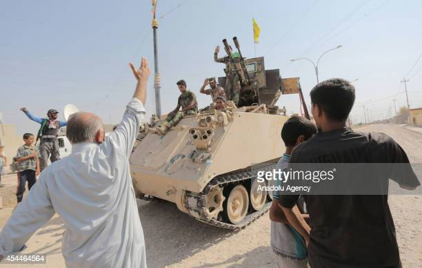 Locals greet the soldiers after Iraqi forces have entered the northern town of Amirli which had been under the siege of Islamic State militants for...