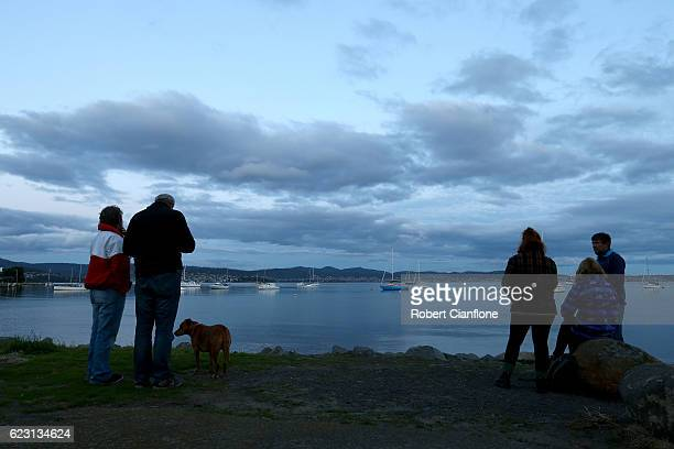Locals hope to catch a glimpse of the super moon as it rises behind cloud over the city of Hobart on November 14 2016 in Hobart Australia A super...