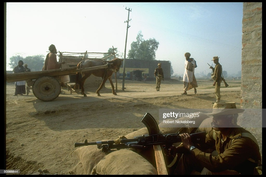 Locals in cart passing Punjab security forces manned sandbagged post in militant Sikh terrorized Bhikhiwind area