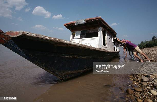 Locals load up a cargo boat on the Mekong River near the picturesque village of Chiang Khan in Loei Province Northeast Thailand From this border...