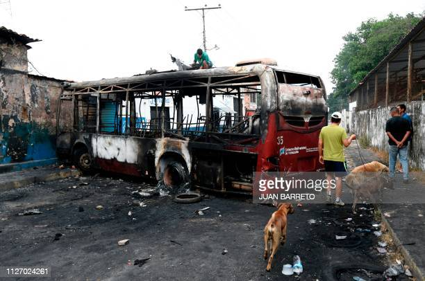 TOPSHOT Locals look at a bus burnt on the eve during protests after President Nicolas Maduro's government ordered a temporary closedown of the border...