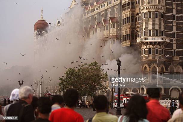 Locals look at a fire as it burns at Taj Mahal Palace & Tower Hotel following an armed siege on November 29, 2008 in Mumbai, India. Indian officials...