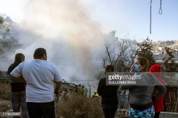 Locals look at firefighters working to extinguish a fire affecting two houses on a hillside at Camino Verde neighborhood in Tijuana, Baja California...