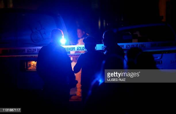 Locals look at mexican forensic staff working at the place where the Guadalajara's police commander Sergio Rivas Mejia and one of his escorts where...