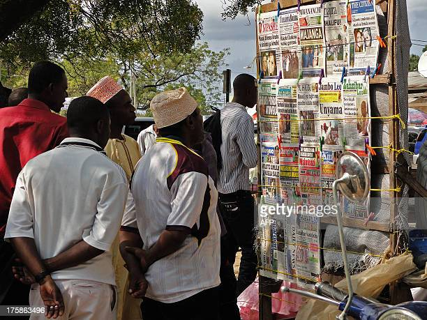 Locals look at newspaper headlines in Stone Town where two young British women suffered an acid attack on the Indian Ocean island of Zanzibar on...