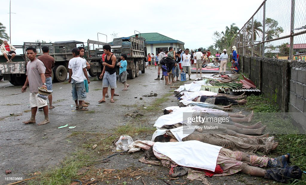 Locals look at the bodies of flood victims at the compound of municipal gymnasium on December 5, 2012 in the southern Philippine township of New Bataan, Compostela province, Philippines. More than 100 people have been killed and scores of others remain missing after Typhoon Bopha, the strongest storm to hit the Philippines this year, pounded the region.