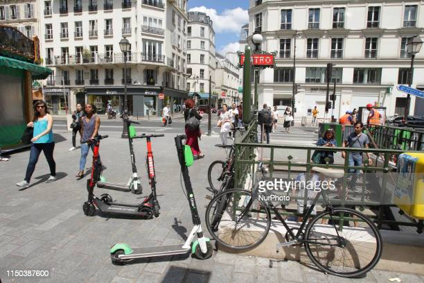 Locals pass past the electric scooters parked on the street at the Saint Paul metro station in Le Mare on June 172019 in ParisFrance Paris is...